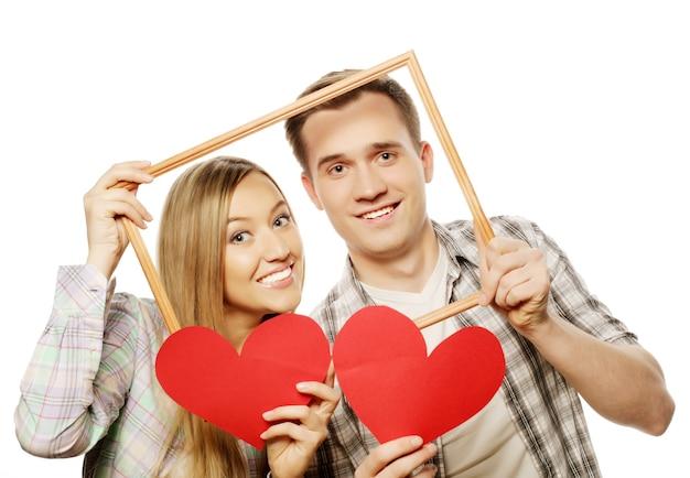 Mooie paar bedrijf frame en rode harten op witte achtergrond.