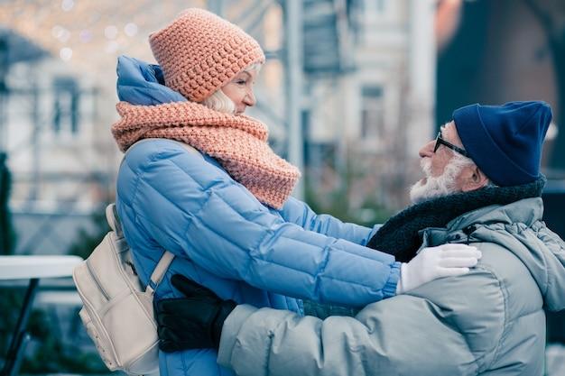 Mooie paar gepensioneerden in winterkleren die buiten staan. vrouw met haar handen op de schouders van haar man