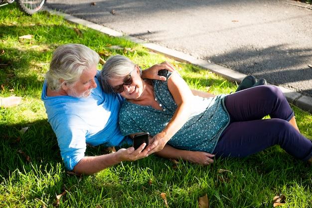 Mooie paar getrouwde senioren die op het gras liggen en naar dezelfde telefoon of hetzelfde apparaat in het park kijken
