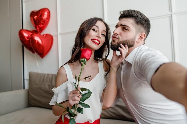 Mooie paar man en vrouw met rode roos en hartvormige ballonnen