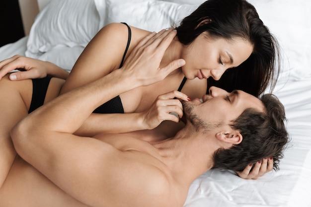Mooie paar man en vrouw samen knuffelen, liggend in bed thuis of hotel appartement