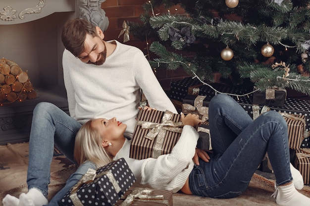 Mooie paar om thuis te zitten in de buurt van de kerstboom