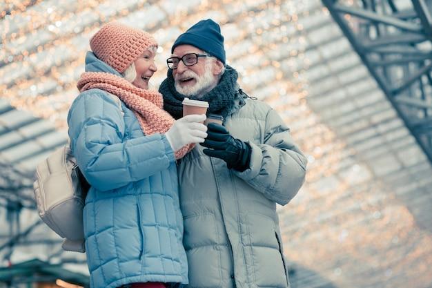 Mooie paar ouderen in warme winterkleren die een wandeling maken met kopjes koffie. verlichting achter hun rug om