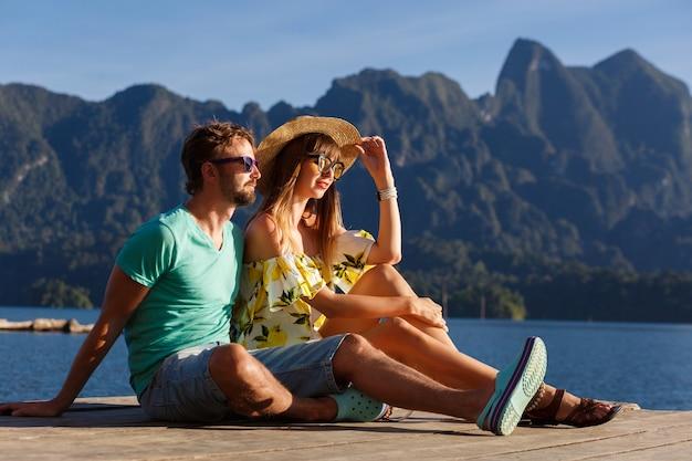 Mooie paar poseren samen de pier voor geweldig uitzicht op bergen, reizende sfeer, stijlvolle zomerkleding en accessoires. khao sok thailand nationaal park.