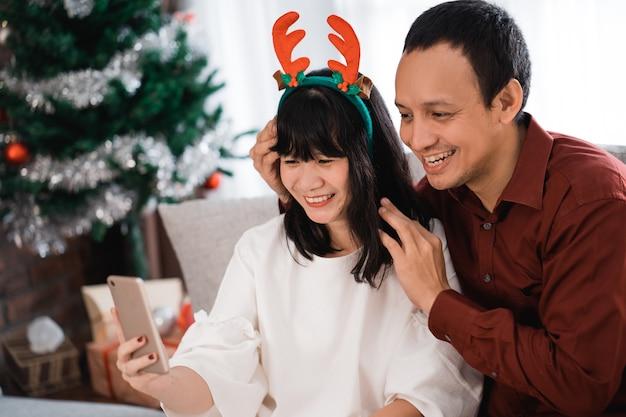 Mooie paar selfie met smartphone in eerste kerstdag