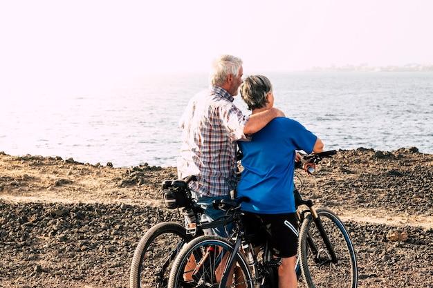 Mooie paar senioren omhelsd op het strand of in een park met hun fietsen - volwassen en actieve mensen trainen en werken hard om fitness te zijn - zee op de achtergrond