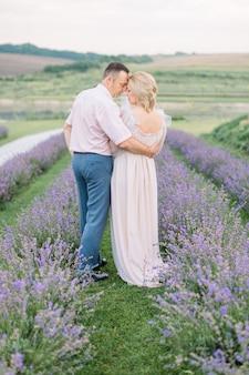 Mooie paar van middelbare leeftijd omarmen op het lavendelveld. liefde, mensen, emoties en lifestyle buitenshuis portret concept