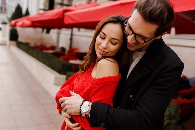 Mooie paar verliefd knuffelen en flirten buiten. romantische momenten. knappe man kijkt op zijn mooie vriendin.
