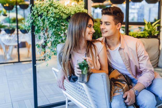 Mooie paar zitten in het café en op zoek naar face to face