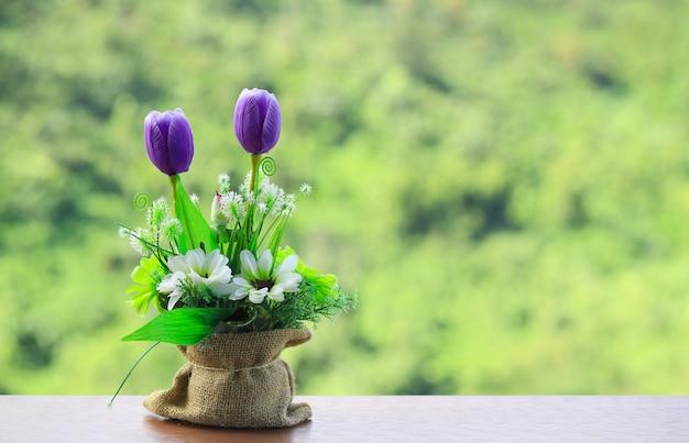 Mooie paarse bloem in zak op houten wazig aard achtergrond, selectieve aandacht, kopie ruimte