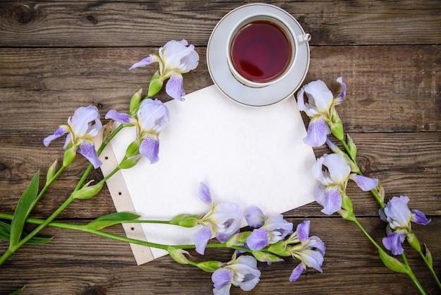 Mooie paarse bloemen irissen, een vel papier en een kopje thee op een houten achtergrond