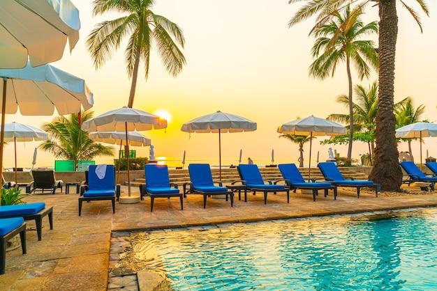 Mooie palmboom met parasol stoel zwembad in luxe hotel resort
