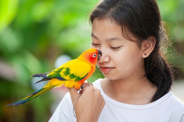 Mooie papegaaivogels die zich op vrouwenhand bevinden. het aziatische spel van het tienermeisje met haar vogel van de huisdierenpapegaai