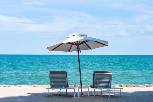 Mooie paraplu en stoel rond strand zee oceaan met blauwe lucht voor reizen