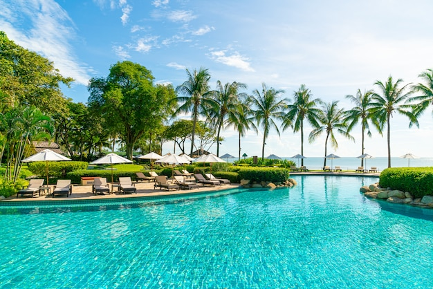 Mooie paraplu en stoel rond zwembad in hotel en resort