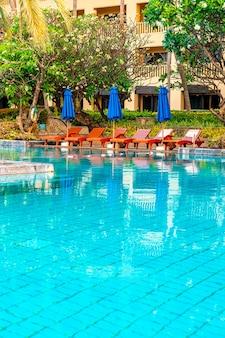 Mooie parasol en stoel rond zwembad in hotel en resort. vakantie en vakantieconcert