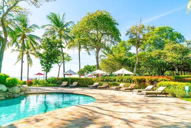 Mooie parasol en stoel rond zwembad in hotel en resort