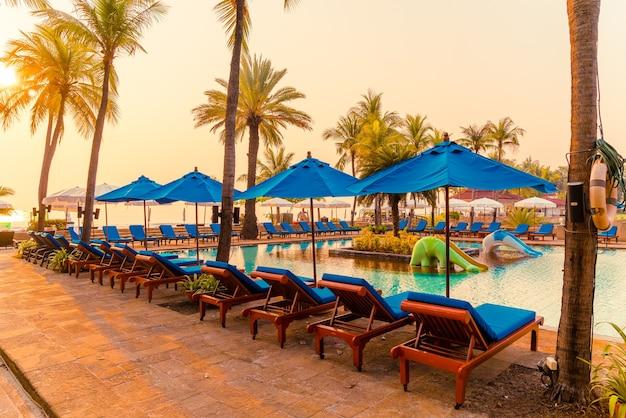 Mooie parasol en stoel rond zwembad in hotel