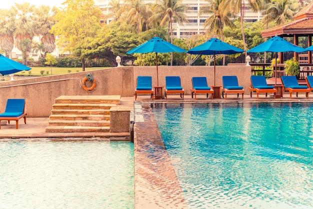 Mooie parasol en stoel rondom zwembad