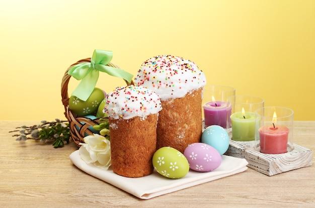 Mooie pasen-cakes, kleurrijke eieren in mand en kaarsen op houten lijst op gele ruimte