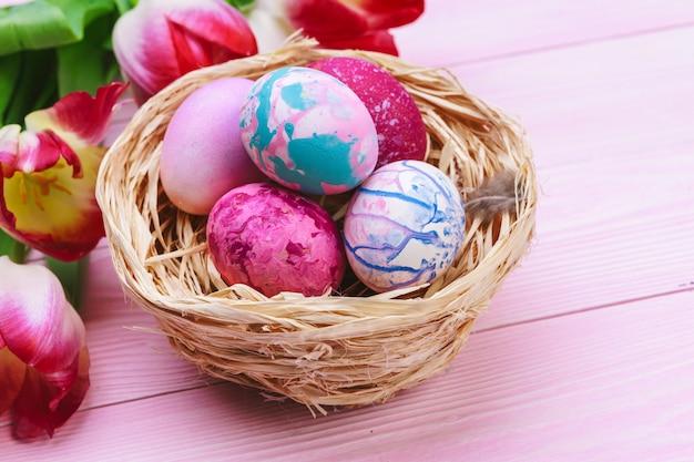 Mooie pasen-samenstelling met verfraaide eieren en bloemen op houten pastelkleur