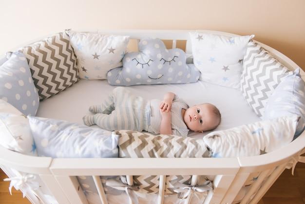 Mooie pasgeboren baby liggend in een ovaal bed met mooie bumpers in delicate grijze, blauwe, witte tinten