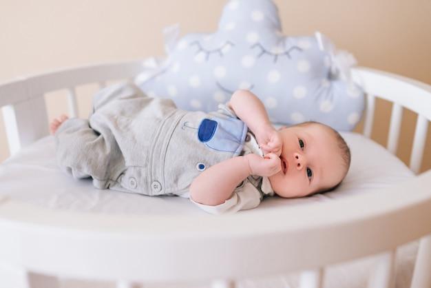 Mooie pasgeboren baby liggend in een rond bed met mooie bumpers in delicate grijze, blauwe, witte tinten