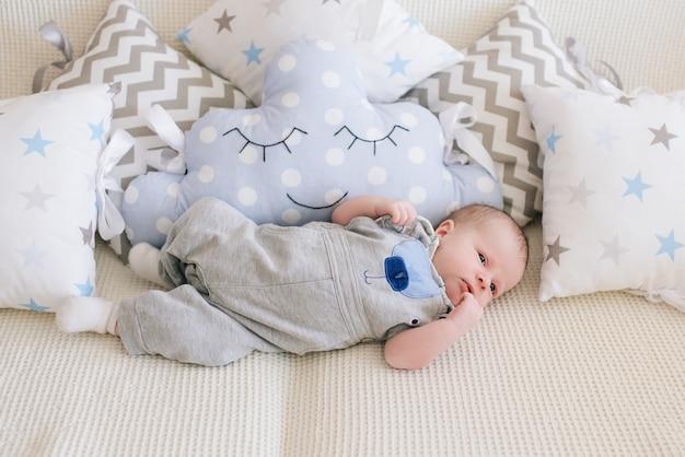 Mooie pasgeboren baby liggend in kussens in delicate grijze, blauwe, witte tinten