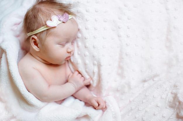 Mooie pasgeboren meisjeslaap op roze deken met plaats voor uw tekst