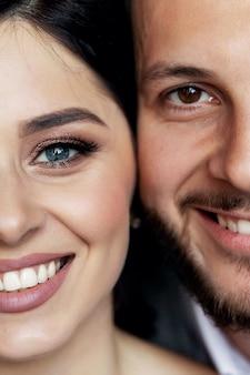 Mooie pasgetrouwden glimlachen. bruiloft idee. bruiloft gezichten. huwelijksfotografie. half gezicht.