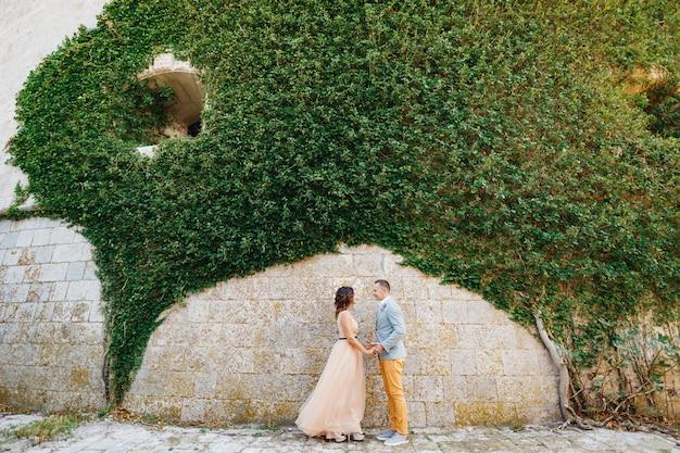 Mooie pasgetrouwden houden elkaars hand vast tegen een stenen muur die is verstrengeld met prachtige groene planten