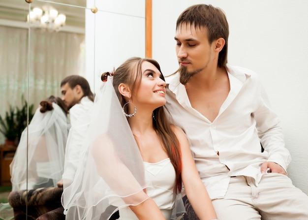 Mooie pasgetrouwden zitten in fauteuil