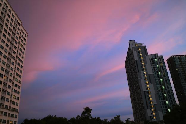 Mooie pastel roze en blauwe wolken laag van de avondrood boven de hoge gebouwen
