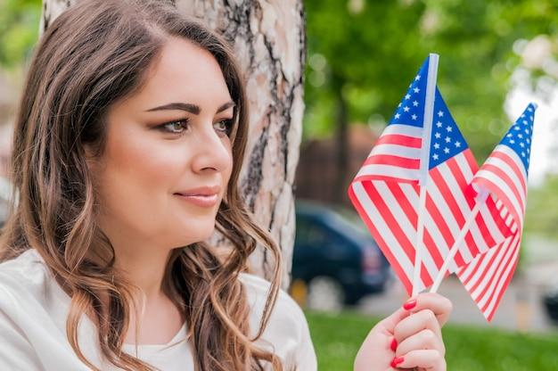 Mooie patriottische jonge vrouw met de amerikaanse vlag