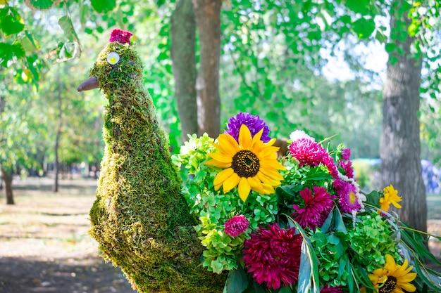Mooie pauwvogel die van verschillende heldere bloemen en groene bladeren wordt gemaakt