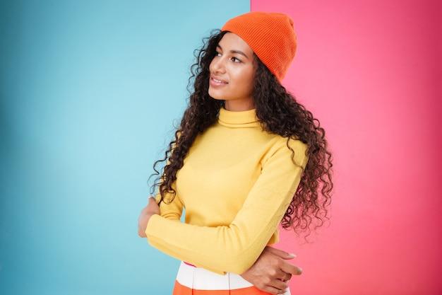 Mooie peinzende afrikaanse jonge vrouw in hoed die staat en denkt