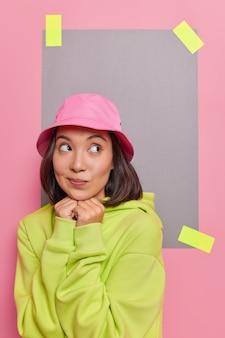 Mooie peinzende aziatische vrouw houdt handen onder de kin denkt over interessante aanbiedingen zoekt naar creatieve oplossing voor probleem draagt groen sweatshirt staat binnen tegen gepleisterd papier