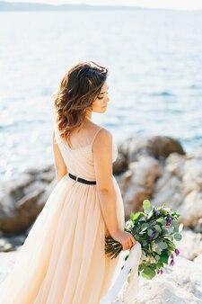 Mooie peinzende bruid staat opzij gedraaid met een boeket bloemen op een rots boven de zee