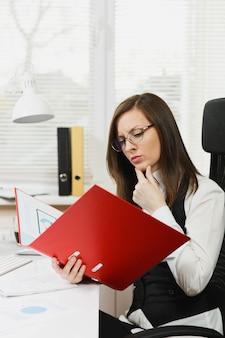Mooie peinzende bruinharige zakenvrouw in zwart-wit pak en bril zittend aan de balie met rode map, mobiele telefoon en kopje koffie, werken op de computer met documenten in licht kantoor.