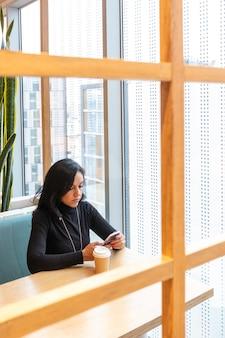 Mooie peinzende brunette vrouw onder het genot van een kopje koffie en herziet uw smartphone