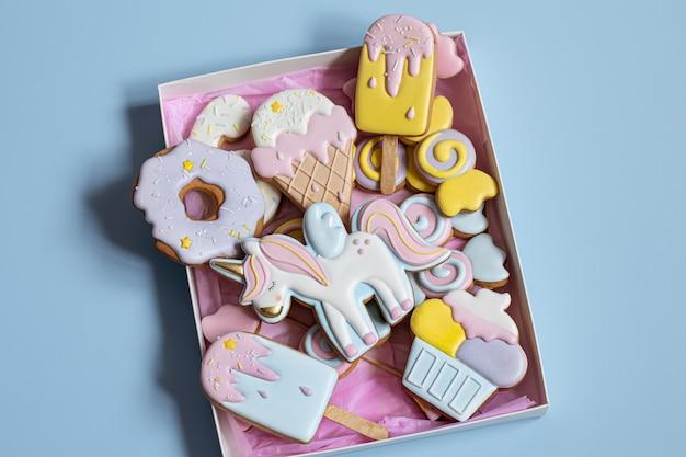 Mooie peperkoekkoekjes voor kinderfeestje in de vorm van een eenhoorn en snoep, platliggend.