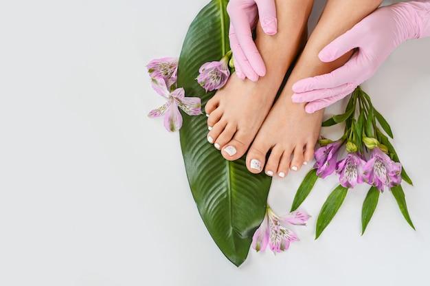 Mooie perfecte huid vrouwelijke benen voeten bovenaanzicht met tropische bloemen en groen palmblad