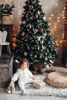Mooie peuter met een pluchen huisdier en een cadeau zittend op het tapijt bij de kerstboom