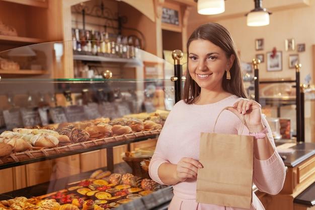 Mooie plus size bochtige vrouw winkelen voor gebak