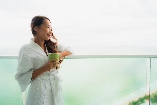 Mooie portret jonge aziatische vrouwen die koffiekop houden bij openluchtbalkon met overzeese oceaanmening