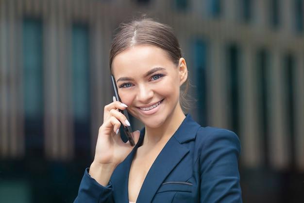 Mooie positieve gelukkige bedrijfsvrouw die op mobiele telefoon spreekt