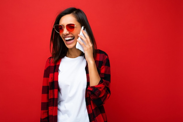 Mooie positieve gelukkige glimlachende jonge donkerbruine vrouw die modieus rood overhemd, witte t-shirt en rode geïsoleerde zonnebril draagt