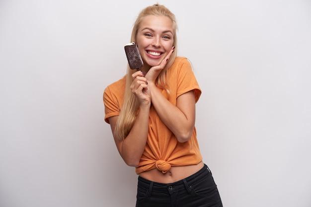 Mooie positieve jonge blonde dame met casual kapsel handpalm op haar wang houden en vrolijk glimlachend naar de camera, ijslollyijs in haar hand houden terwijl geïsoleerd op witte achtergrond