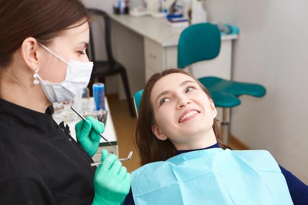 Mooie positieve jonge vrouw die breed glimlacht na regelmatige tandcontrole, die haar vrouwelijke hygiënist bekijkt, haar perfecte witte tanden toont