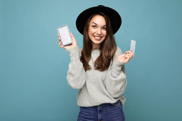 Mooie positieve lachende jonge brunette vrouw met zwarte hoed en grijze trui geïsoleerd over